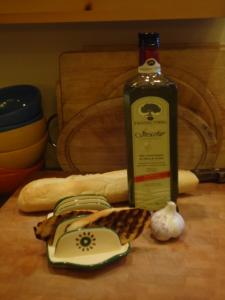 Bruschetta bread on a plate with a loaf of french breach & bottle of olive oil on a table.