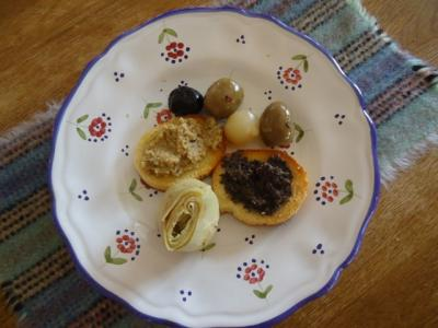 Plate of Crostini with Olive Paste and black and green olives as garnish.